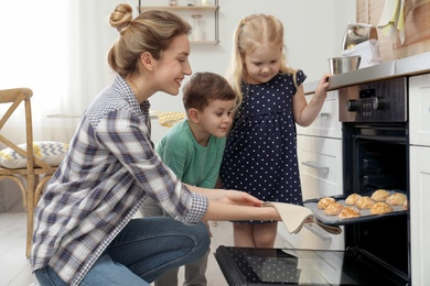 Mother and her children taking out cookies from oven in kitchen