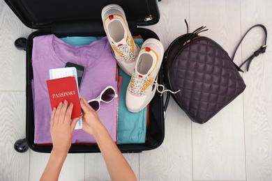 Woman packing suitcase for journey on wooden floor, top view