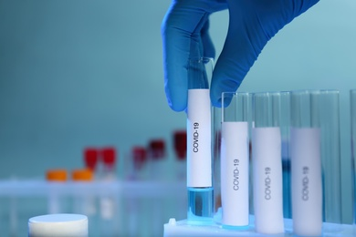 Scientist taking test tube with label Covid-19 from holder on blurred background, closeup. Space for text