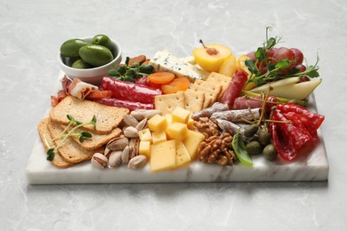 Board with different tasty appetizers on light marble table