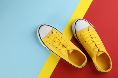 Pair of trendy sneakers on color background, flat lay. Space for text