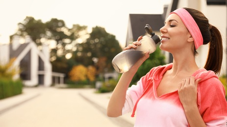 Beautiful sporty woman drinking water after running on street. Healthy lifestyle