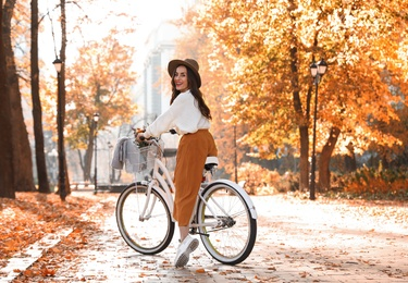 Beautiful happy woman riding bicycle in autumn park