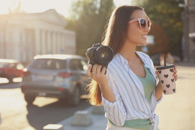Young photographer with professional camera and drink outdoors. Space for text