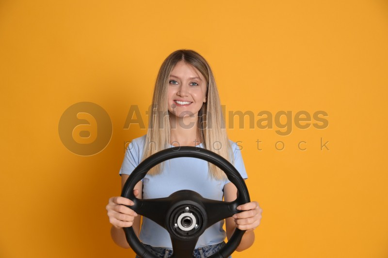 Happy young woman with steering wheel on yellow background