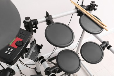 Modern electronic drum kit near white wall indoors. Musical instrument