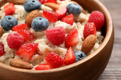Tasty oatmeal porridge with berries and almond nuts in bowl, closeup