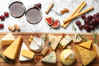 Flat lay composition with different types of delicious cheese on marble table