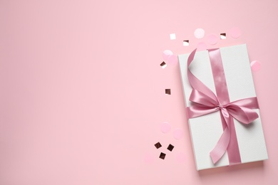 Beautiful gift box and confetti on pink background, flat lay. Space for text