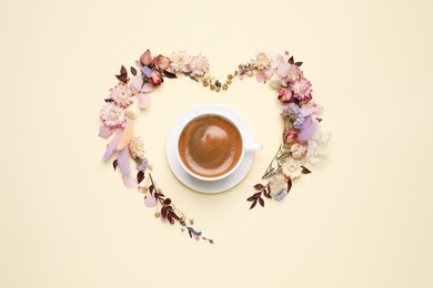 Beautiful heart shaped floral composition with cup of coffee on beige background, flat lay