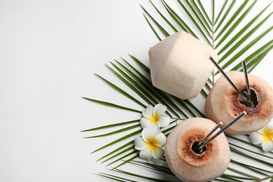 Fresh coconuts with drinking straws and flowers on white background, flat lay. Space for text