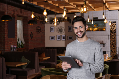 Young business owner with tablet in his cafe. Space for text