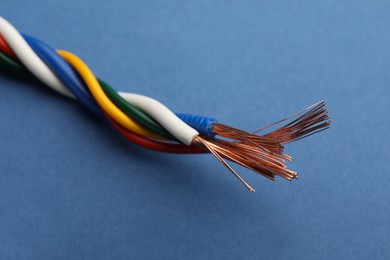 Many twisted electrical wires on blue background, closeup