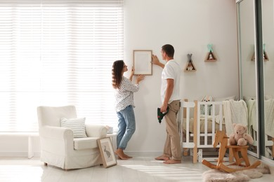 Happy couple decorating baby room with pictures together. Interior design