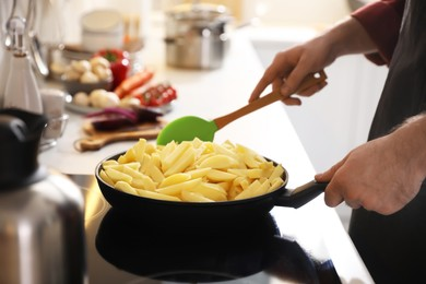 Man stirring cut raw potatoes in frying pan, closeup