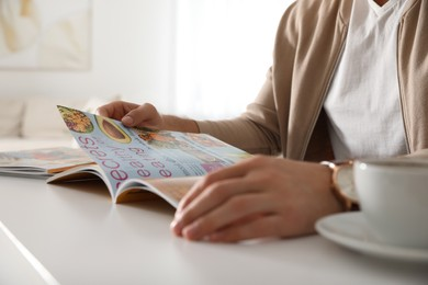 Man reading culinary magazine at white table indoors, closeup
