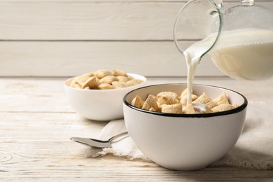 Pouring milk into bowl of tasty corn pads served on white wooden table. Space for text