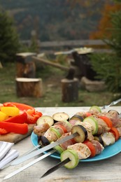 Metal skewers with raw marinated meat and vegetables on wooden table outdoors