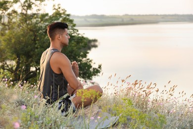 Man meditating in meadow near river. Space for text