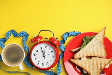 Flat lay composition with tasty sandwiches and alarm clock on yellow background, space for text. Nutrition regime