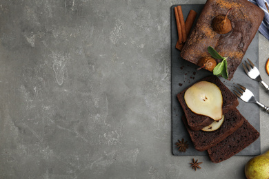Flat lay composition with tasty pear bread on grey table, space for text. Homemade cake