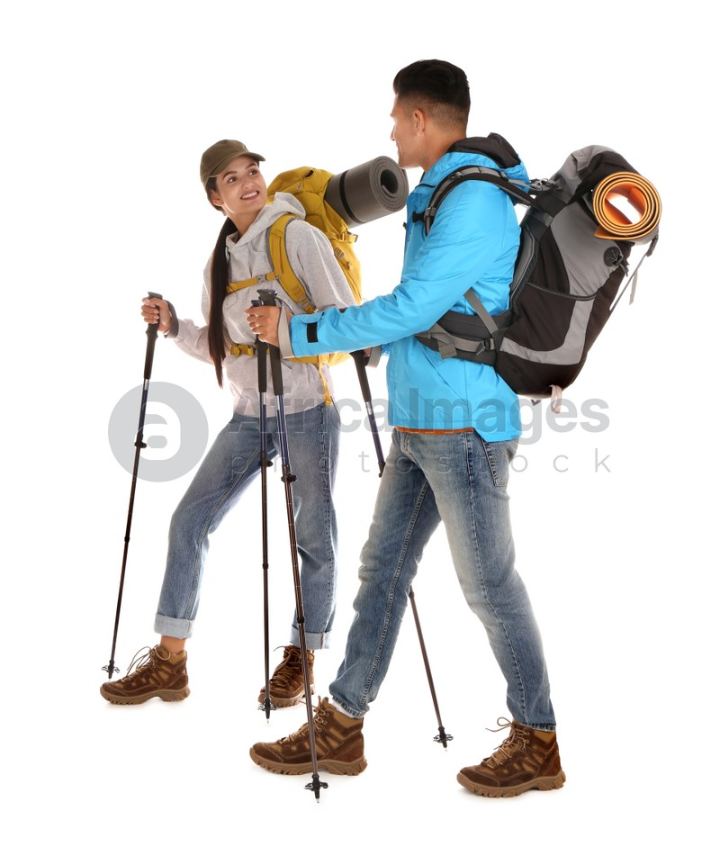 Couple of hikers with backpacks and trekking poles on white background