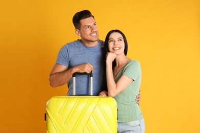 Happy couple with suitcase for summer trip on yellow background. Vacation travel