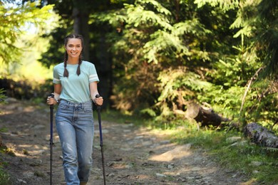Woman with trekking poles hiking in forest