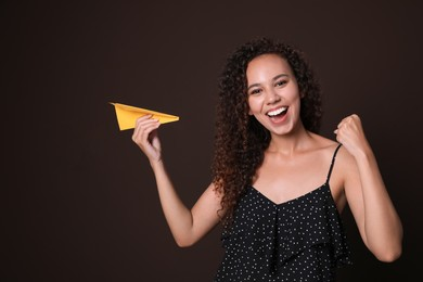 Beautiful African-American woman playing with paper plane on brown background