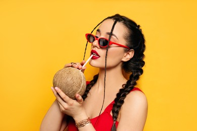 Young woman with fresh coconut on yellow background. Exotic fruit