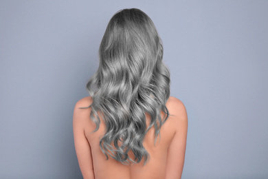 Woman with gray hair on grey background, back view