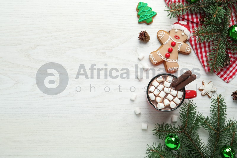 Delicious hot chocolate with marshmallows and cocoa sticks near Christmas decor on white wooden table, flat lay. Space for text