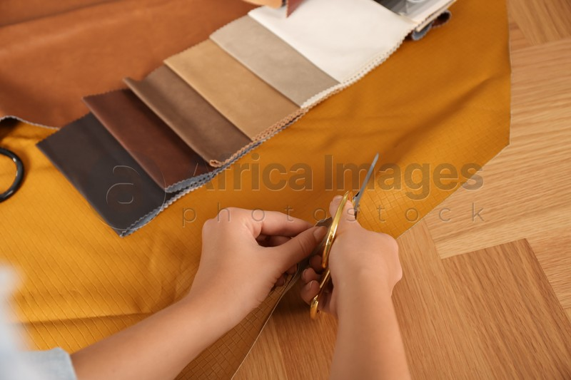 Woman cutting orange leather with scissors at wooden table, closeup