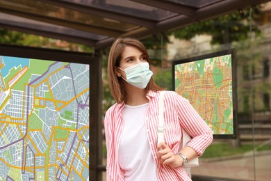 Young woman in protective mask waiting for public transport at bus stop