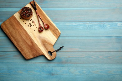Cutting board, peppercorn and spoons on blue wooden table, top view with space for text. Cooking utensils