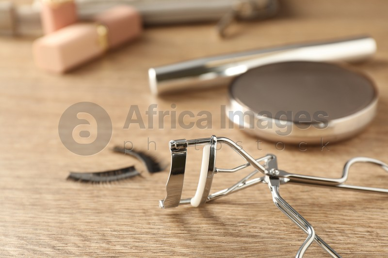 Eyelash curler on wooden table, closeup. Space for text
