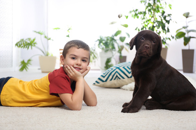 Little boy with puppy on floor at home. Friendly dog