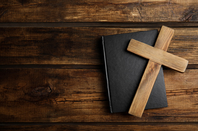 Christian cross and Bible on wooden background, top view with space for text. Religion concept