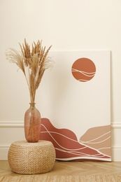 Fluffy reed plumes and painting near white wall indoors. Interior elements
