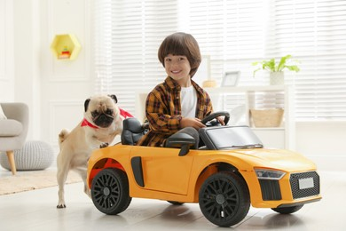 Little boy with his dog in toy car at home