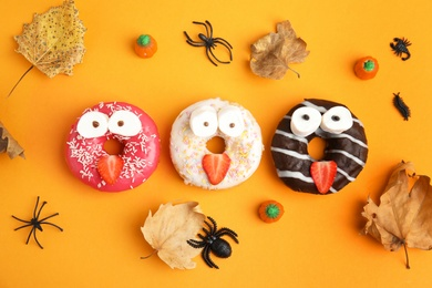 Delicious donuts decorated as monsters on orange background, flat lay. Halloween treat