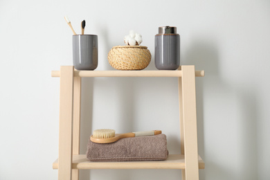 Wooden shelving unit with toiletries near white wall indoors. Bathroom interior element
