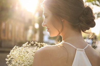 Bride in beautiful wedding dress with bouquet outdoors, closeup