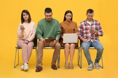 People waiting for job interview on yellow background
