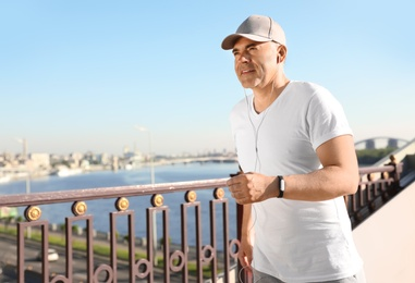 Handsome mature man running on bridge, space for text. Healthy lifestyle