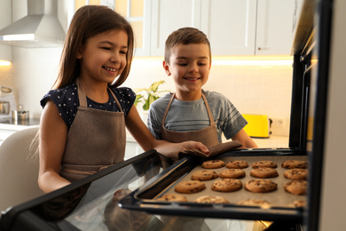 Cute little children taking cookies out of oven in kitchen. Cooking pastry