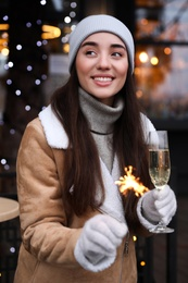 Happy young woman with sparkler and glass of champagne at winter fair