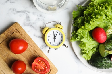 Alarm clock and vegetables on white marble table, flat lay. Meal timing concept
