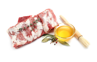 Raw ribs with herbs and oil on white background