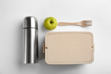 Thermos, lunch box and apple on white background, top view